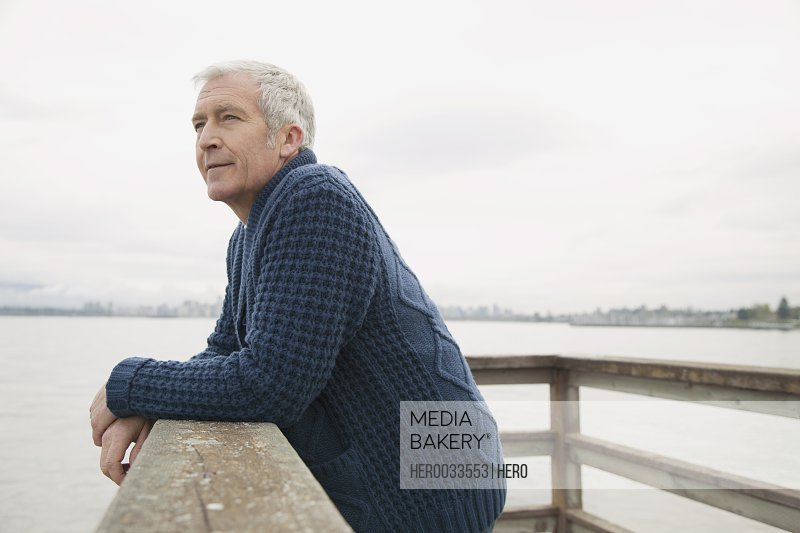 mature man leaning on the railing at the dock