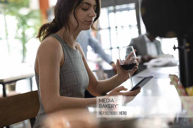 Businesswoman texting on phone with red wine