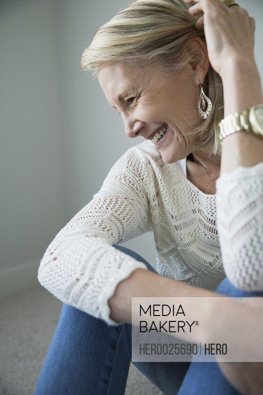 Senior woman laughing hugging knees
