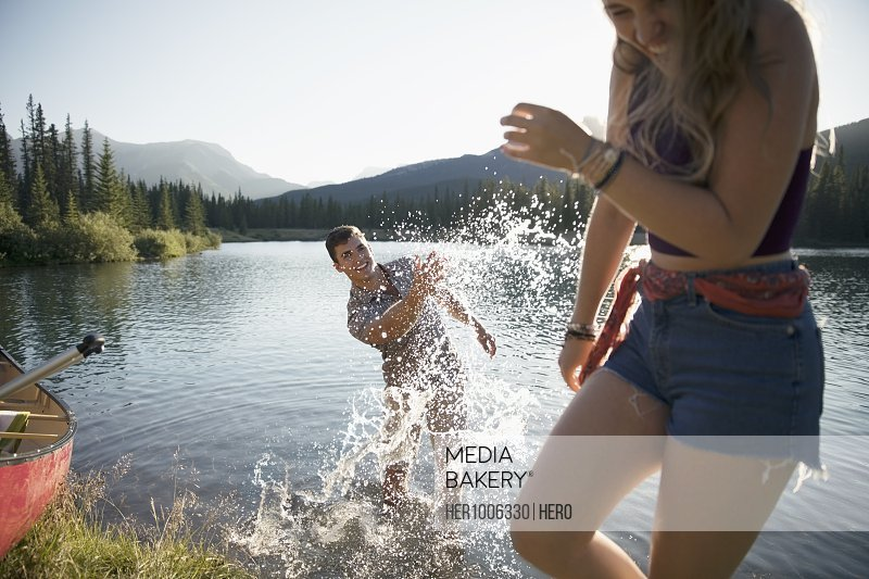 Playful young couple splashing water at sunny summer lake