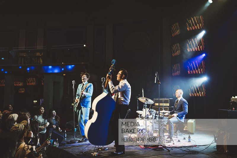Rockabilly musicians performing on stage at music concert