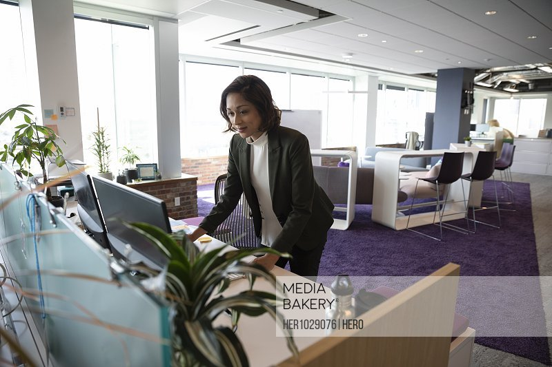 Mid adult businesswoman using computer in open plan office