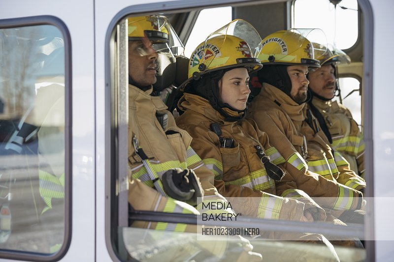 Firefighters riding in fire engine