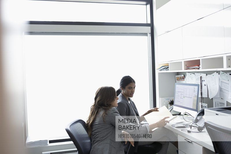 Female doctors discussing medical record in clinic office
