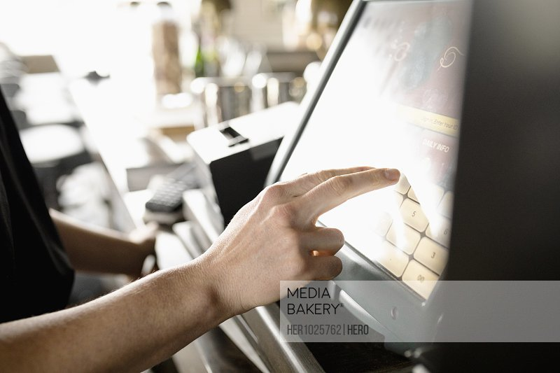 Close up server using touch screen computer in restaurant
