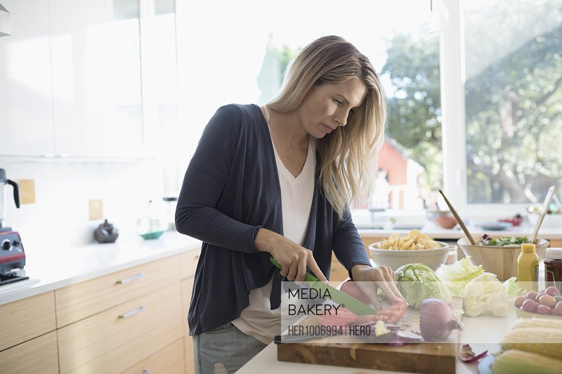 Woman cooking, cutting vegetables on cutting board at kitchen counter