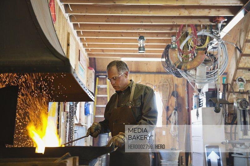 Welder working at blacksmith forge at workshop