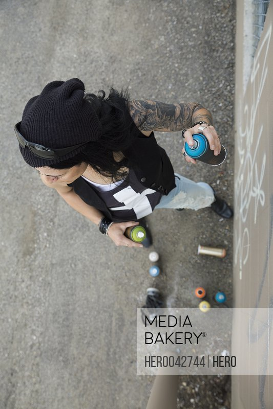 Mature female graffiti artist spray painting wall