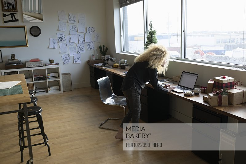 Young woman with blonde curly hair working at laptop in studio