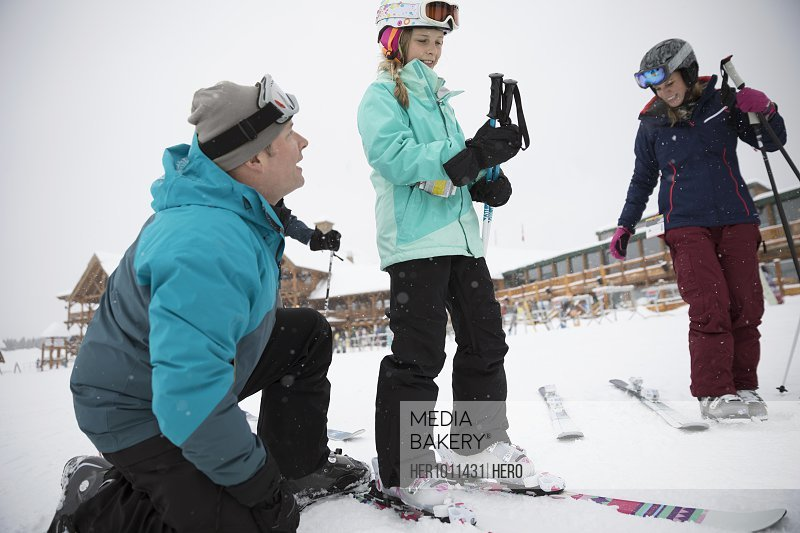 Father helping daughter skier preparing skis