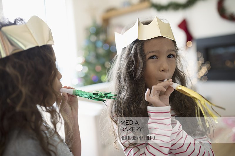 Sisters in paper Christmas crowns playing with party favors
