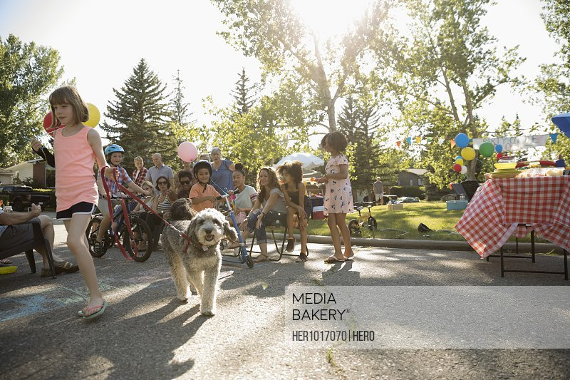 Kids and dog parade at summer neighborhood block party in sunny park