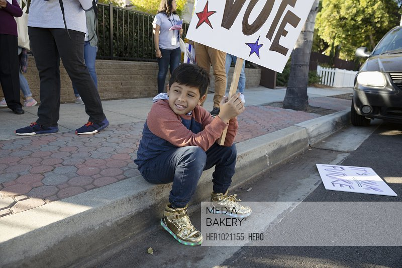 Latinx boy volunteering, canvassing voters on curb