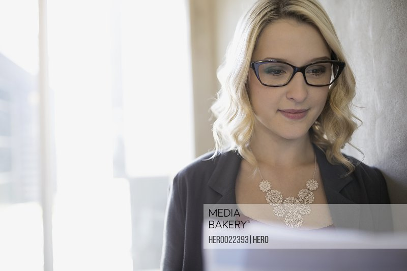 Focused blonde businesswoman reading paperwork
