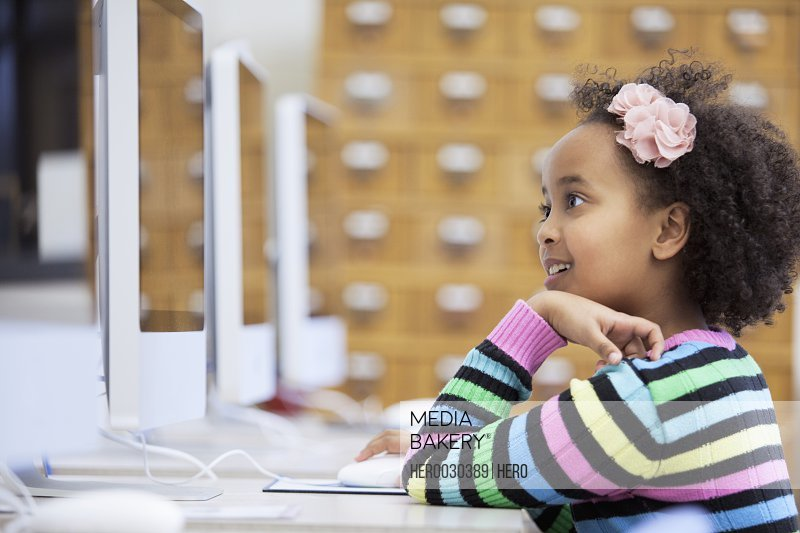 cute elementary student using computer