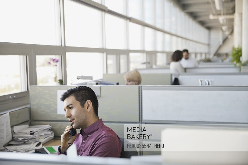 Businessman answering telephone in office cubicle