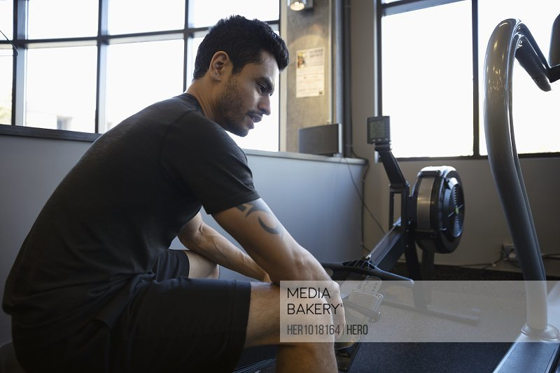 Man exercising, resting on rowing machine in gym