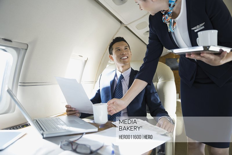 Flight attendant serving businessman on corporate jet