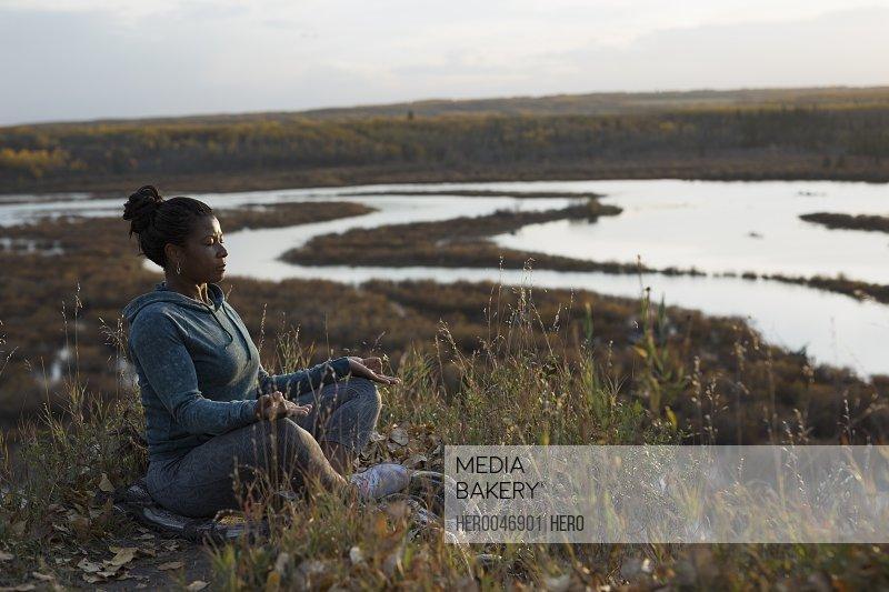 Serene woman meditating in lotus position on autumn hillside overlooking lake