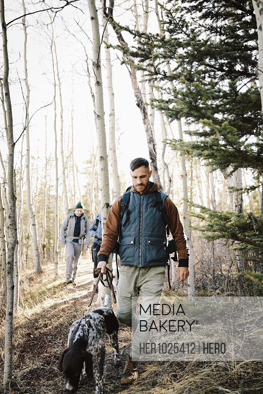Man with dog hiking in woods