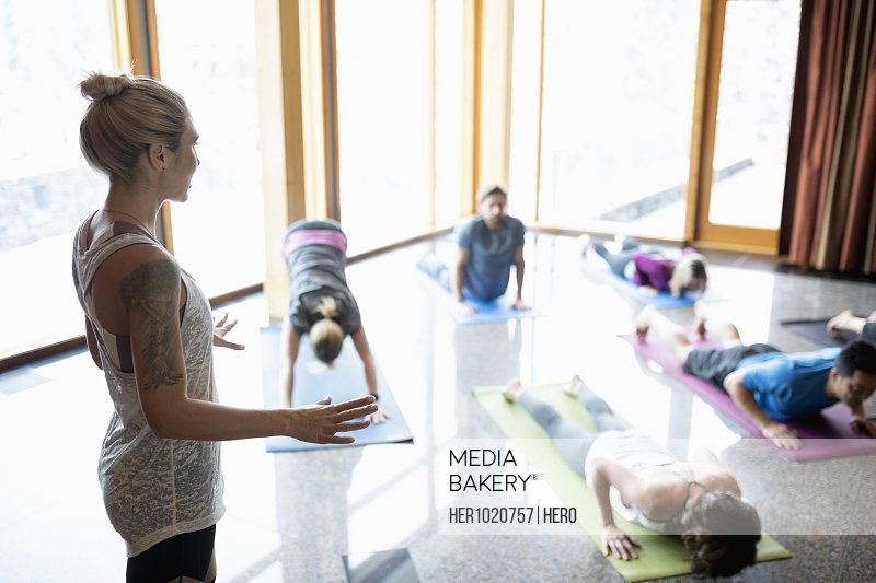 Female instructor leading yoga class practicing plank pose in studio