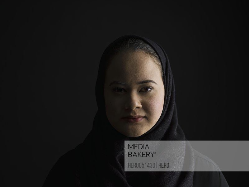 Portrait serious Middle Eastern woman wearing black hijab in shadow against black background