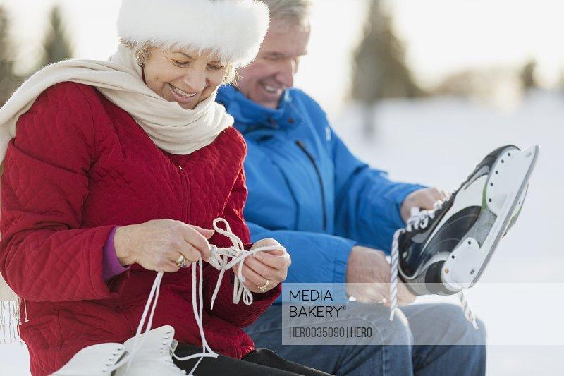 Senior couple putting on ice skates