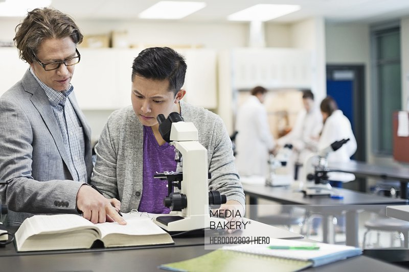 Professor helping male student in college science lab