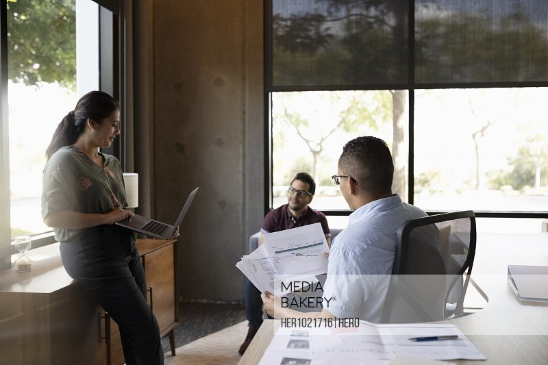 Business people meeting, discussing paperwork in office