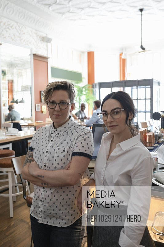 Portrait of restaurant owner and waitress looking at camera