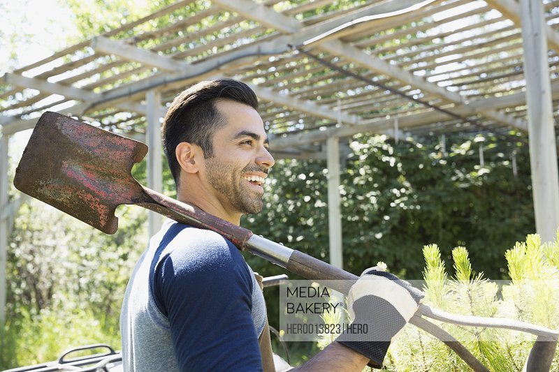 Smiling worker with shovel at plant nursery