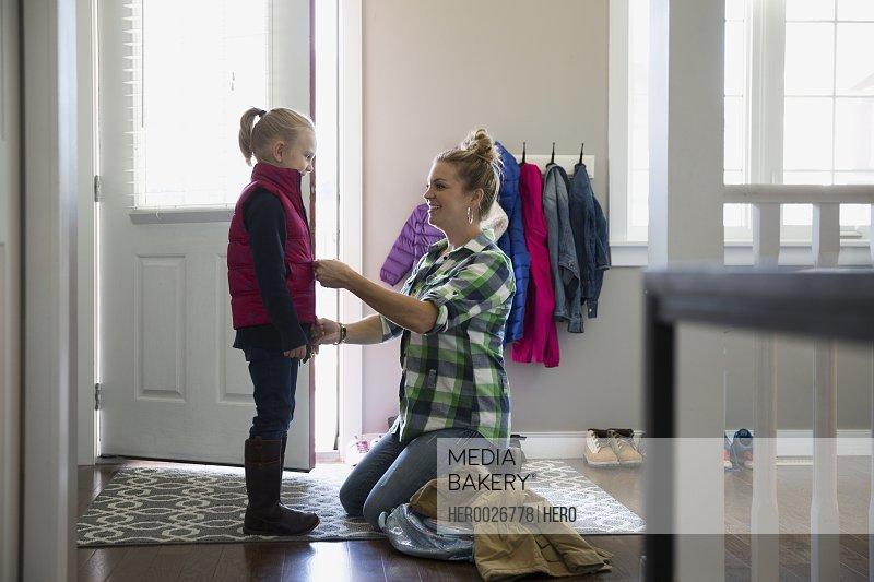 Mother zipping vest on daughter at front door