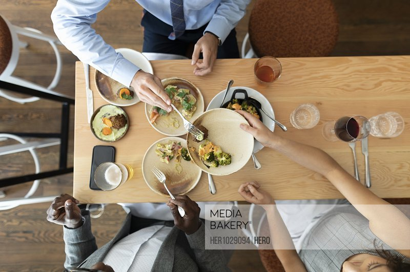 Overhead view of business colleagues eating lunch in restaurant