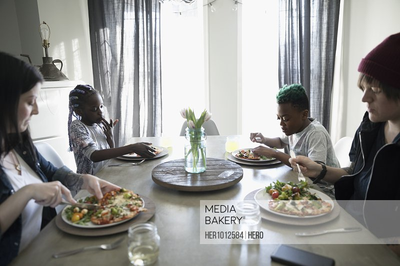 Homosexual couple and children eating dinner