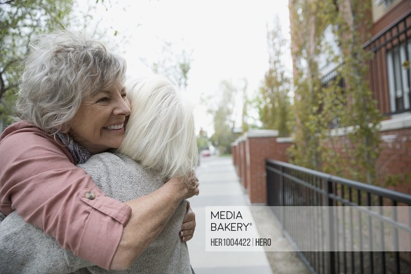 Smiling senior women hugging on urban sidewalk