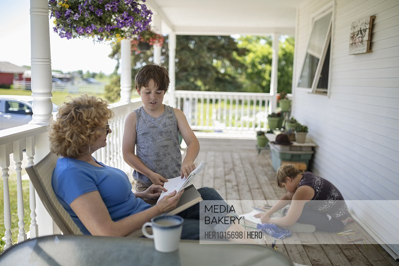 Grandson showing drawing to grandmother on porch