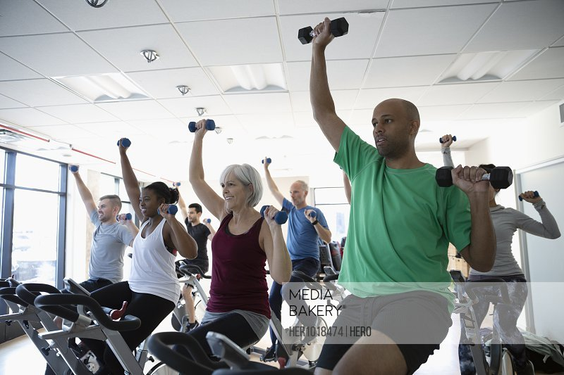 People using dumbbells on exercise bikes in spin class in gym