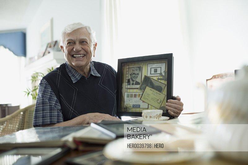 Smiling senior man holding old memorabilia