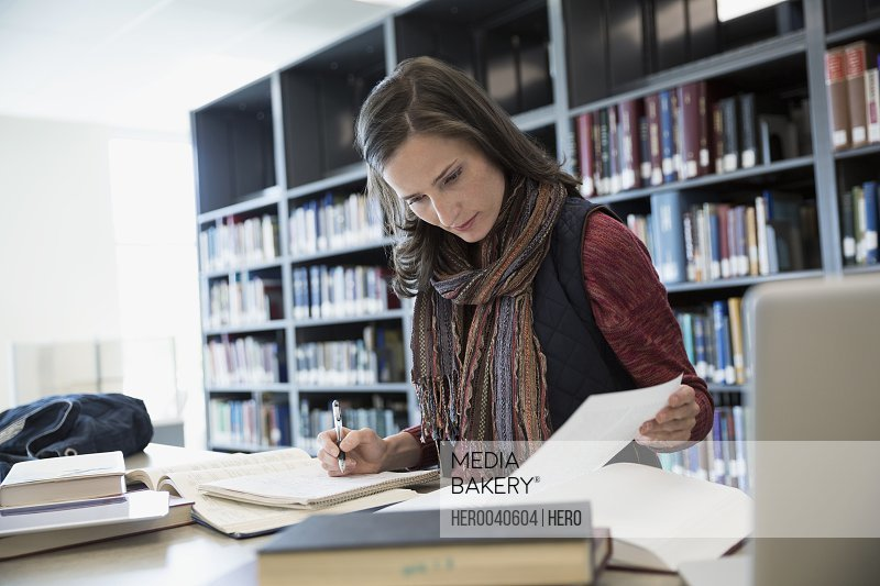 Focused adult education student researching in library