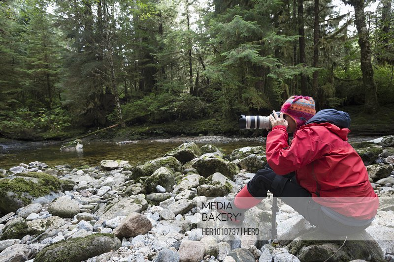 Female photographer with digital camera and lens photographing on rocks along wilderness stream
