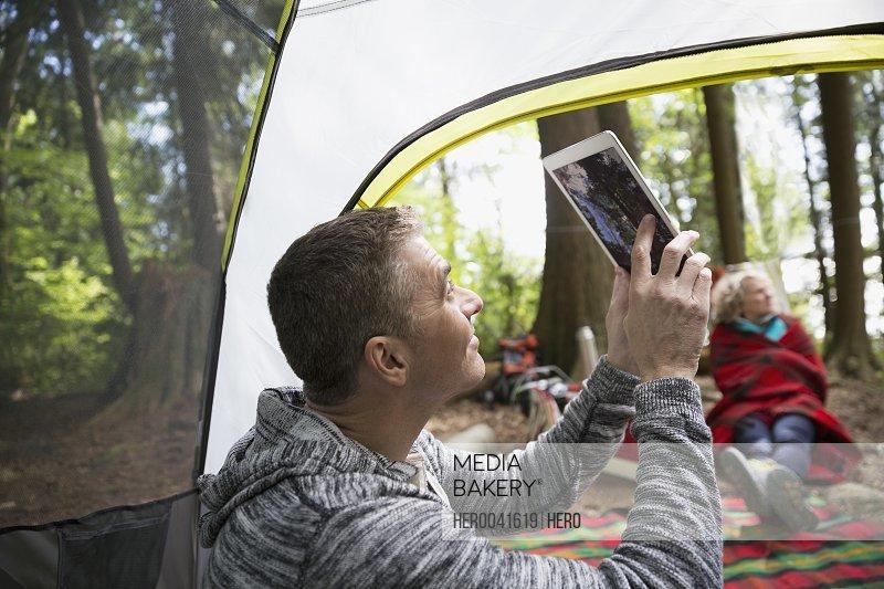 Man using digital tablet camera inside camping tent