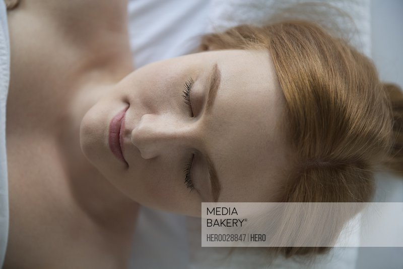 Overhead view serene woman eyes closed massage table