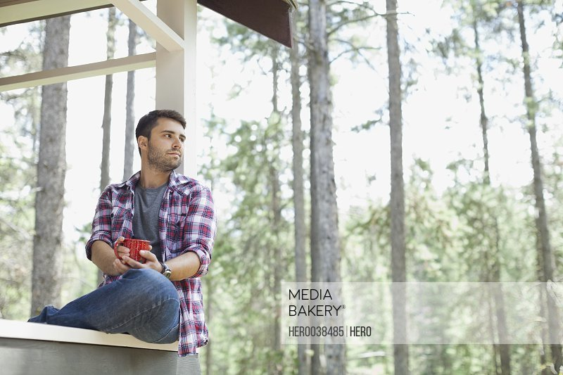 Man sitting on cabin porch with coffee cup