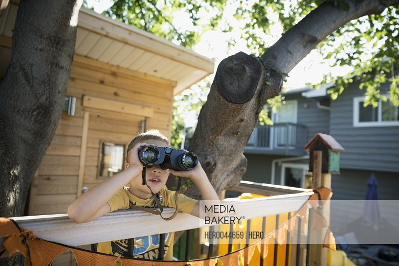Boy with binoculars in treehouse