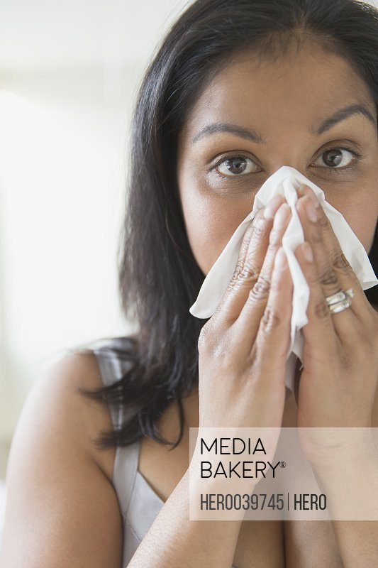 Mid adult woman blowing nose into tissue