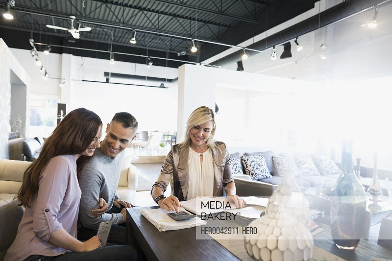 Interior designer working with couple in home furnishings store