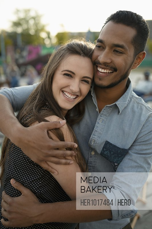 Portrait affectionate young couple hugging