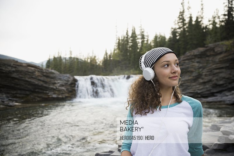 Teenage girl listening to music with headphones near remote waterfall