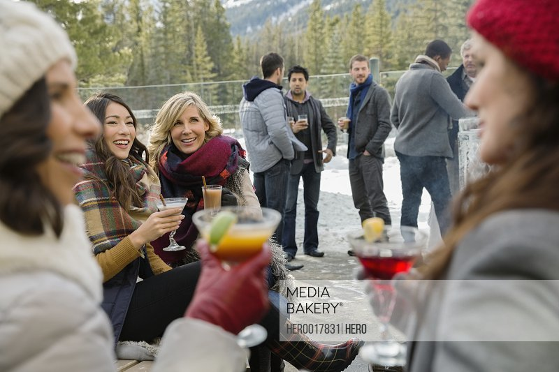 Friends in warm clothing drinking on patio