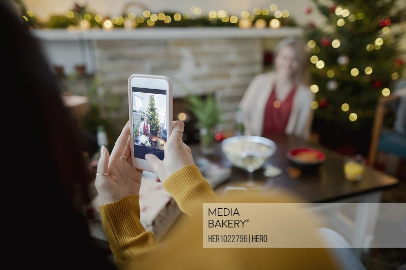 Woman with camera phone photographing friend in Christmas living room